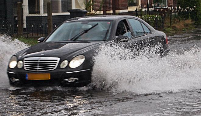 black mercedes car driving through flood water down a street