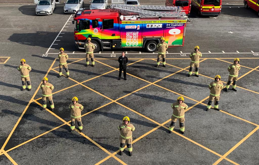 11 trainees in fire kit, stand the the Chief Fire Officer in uniform in front of a multicoloured fire engine.