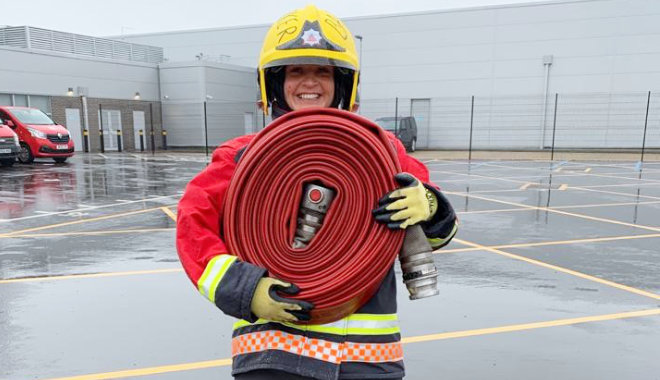 katie in firefighter kit smiling and holding a rolled up fire hose on training ground