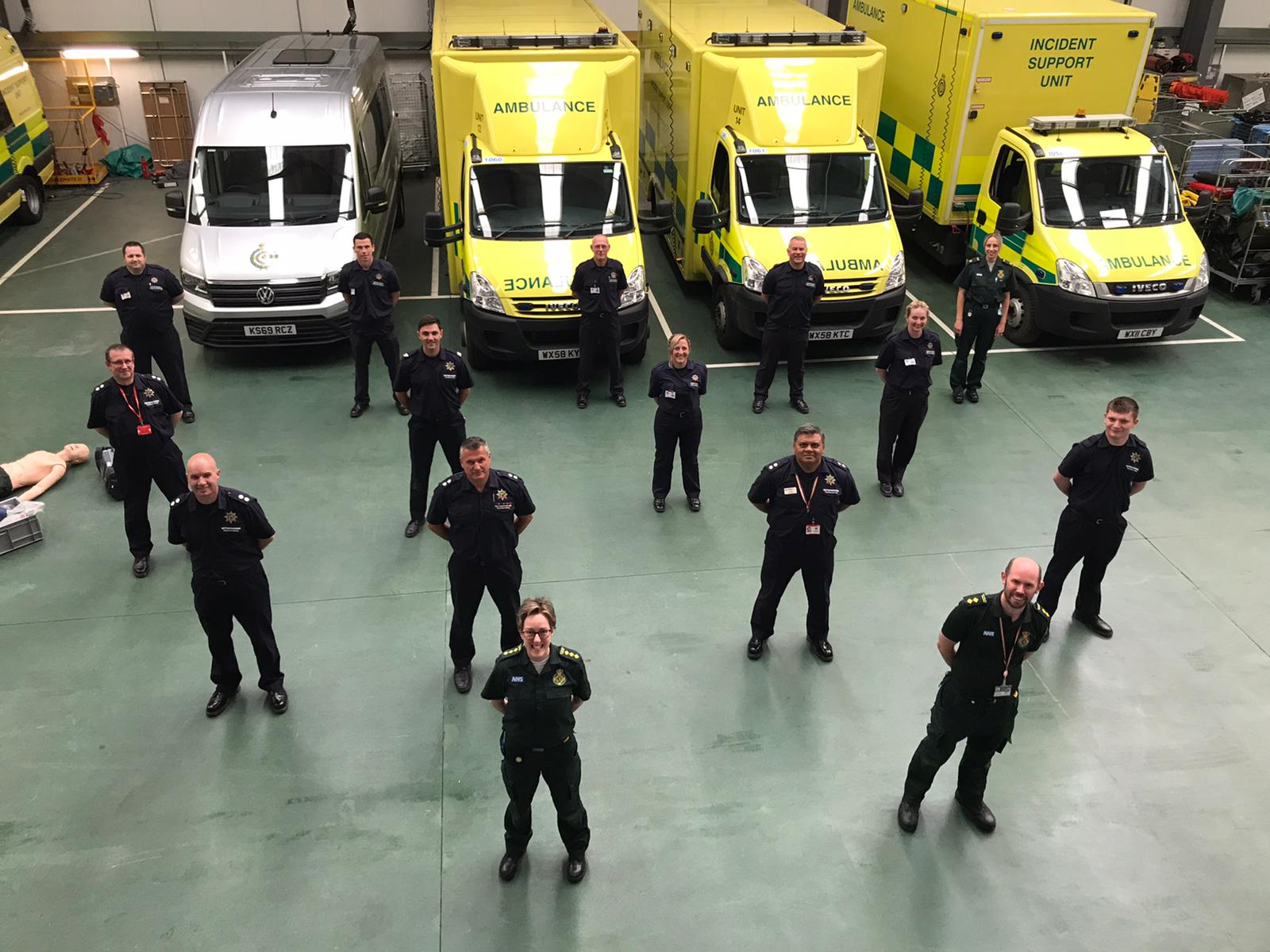 13 fire service members and 2 emas members stood 2m apart in front of ambulance vehicles