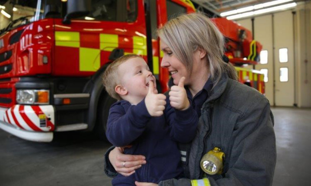 Jo crouching in front of fire engine holding young son