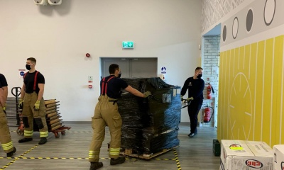 Firefighters in stores moving testing equipment