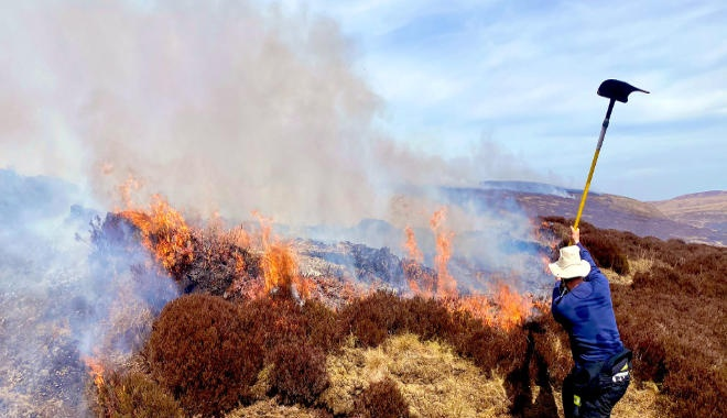 lone firefighter fighting moorland blaze